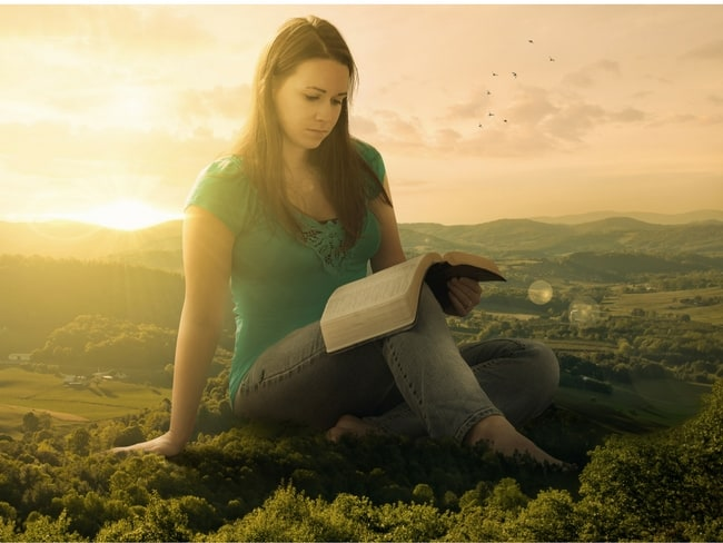 woman reading a bible in a field.