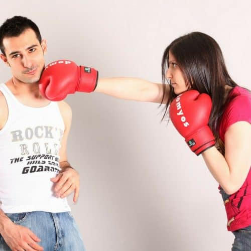 Young Woman Punching Young Male Wearing Red Boxing Gloves