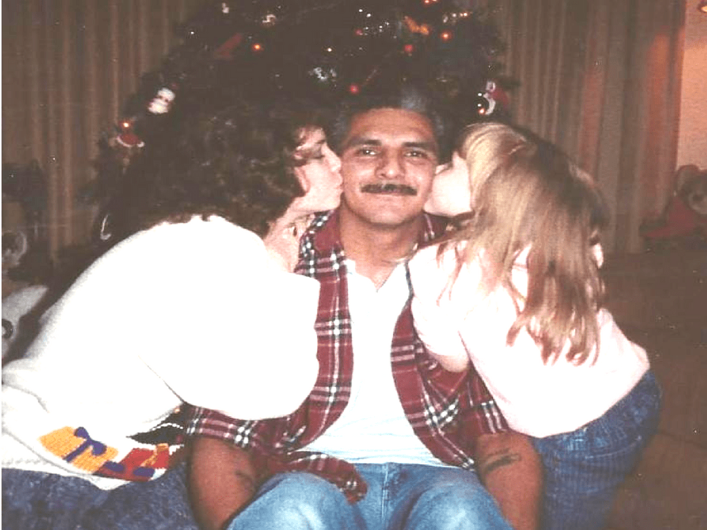 Two young girls kissing their father on the cheek.