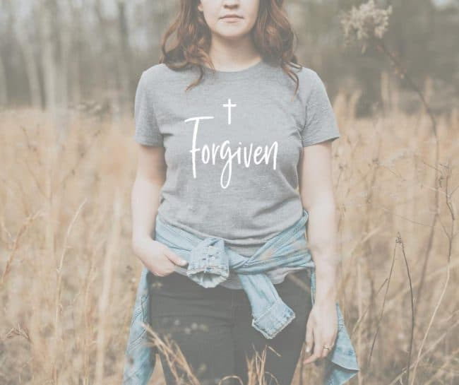 Woman in gray tee shirt with word written in white that says forgiveness in a fall field.