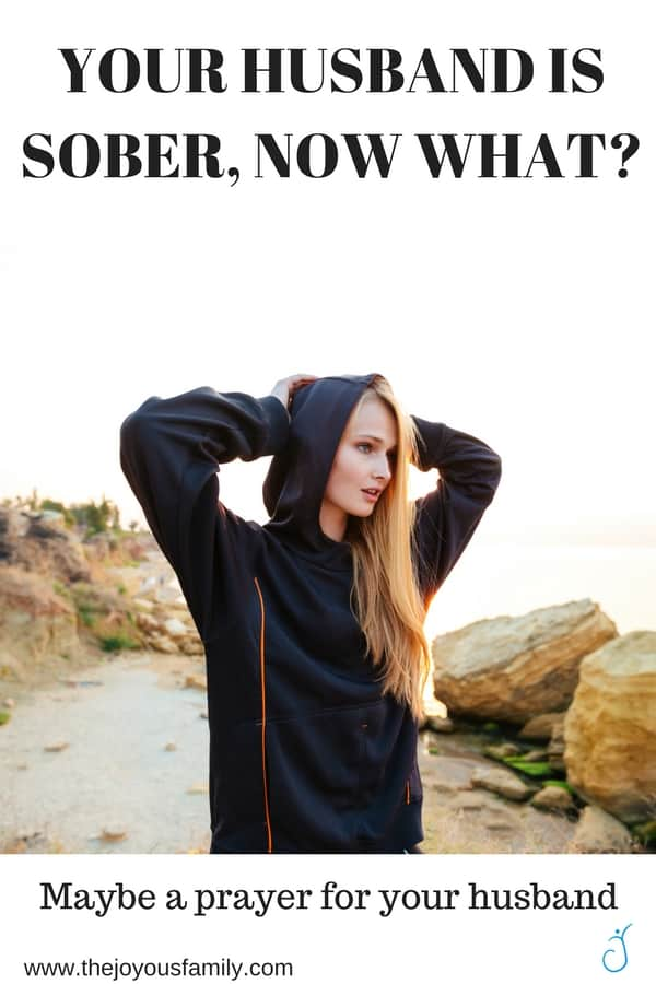 blond woman in black hoodie with hands on her head looking out over the ocean.