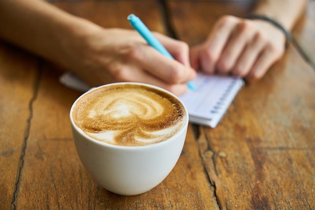 Cup of coffee and person writing on a note pad. Just see the hands and coffee.