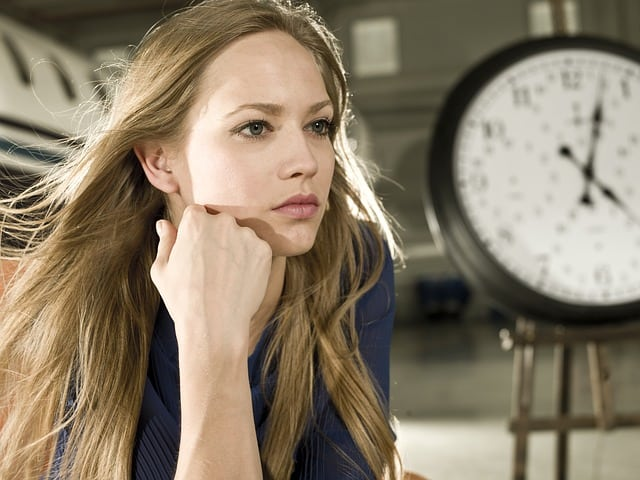 Blonde woman staring out in space with a clock behind her.