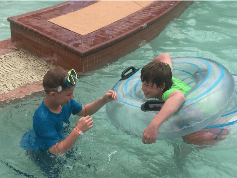 boys playing in a pool for article on not beating yourself up when parenting