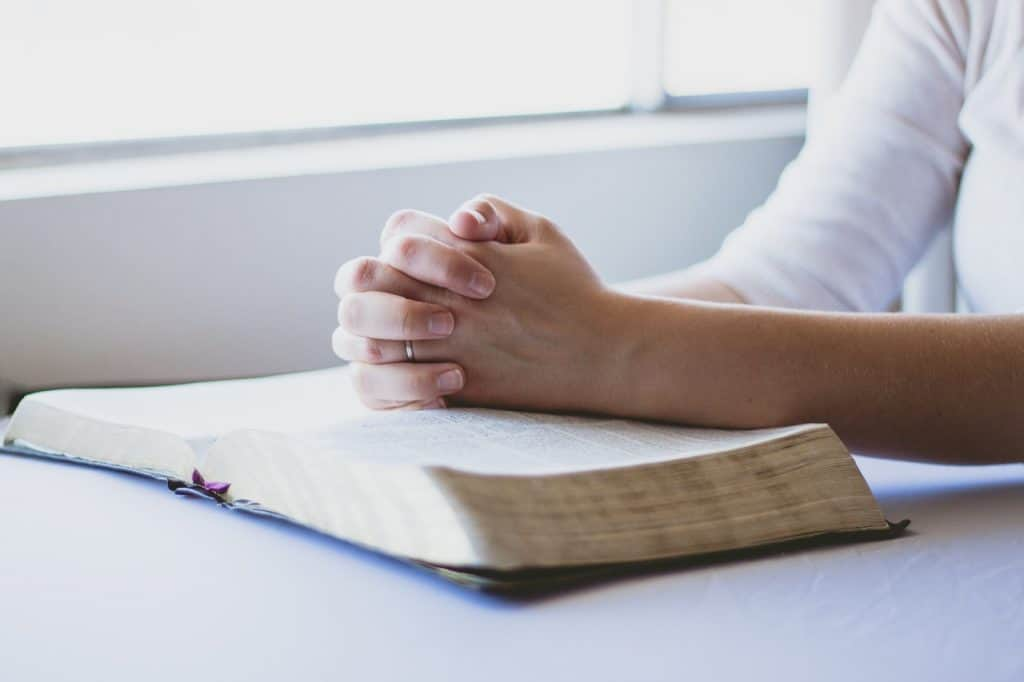 Woman hands folded in prayer over a bible
