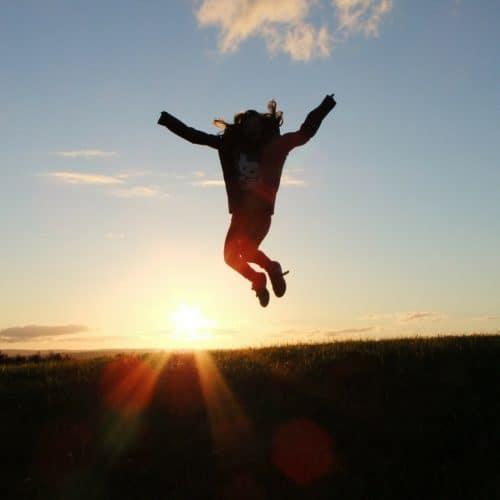 Woman jumping at sun rise
